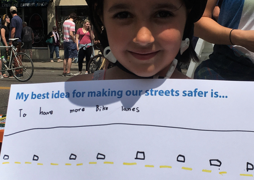 "Child wearing helmet holding sign that says ""My best idea for making our streets safer is ""to have more bike lanes"" with drawing of a road."