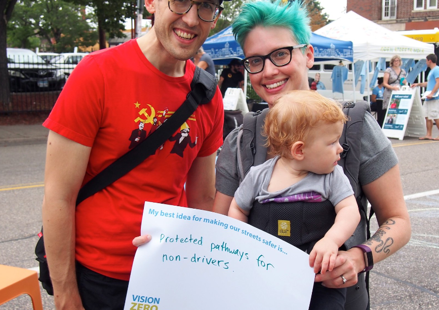 "Two adults and a baby. Adult is holding sign that says: ""My best idea for making our streets safer. Protected pathways for non-drivers."""