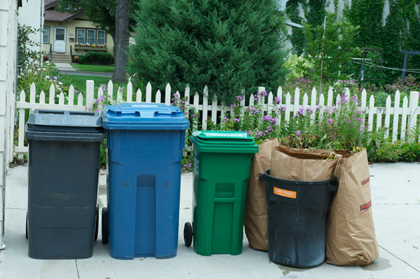 garbage, recycling, organics carts and yard waste bags outside of someone's home