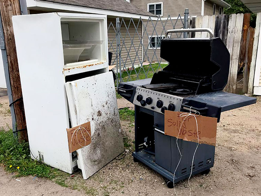 Image of refrigerator and grill set out for recycling